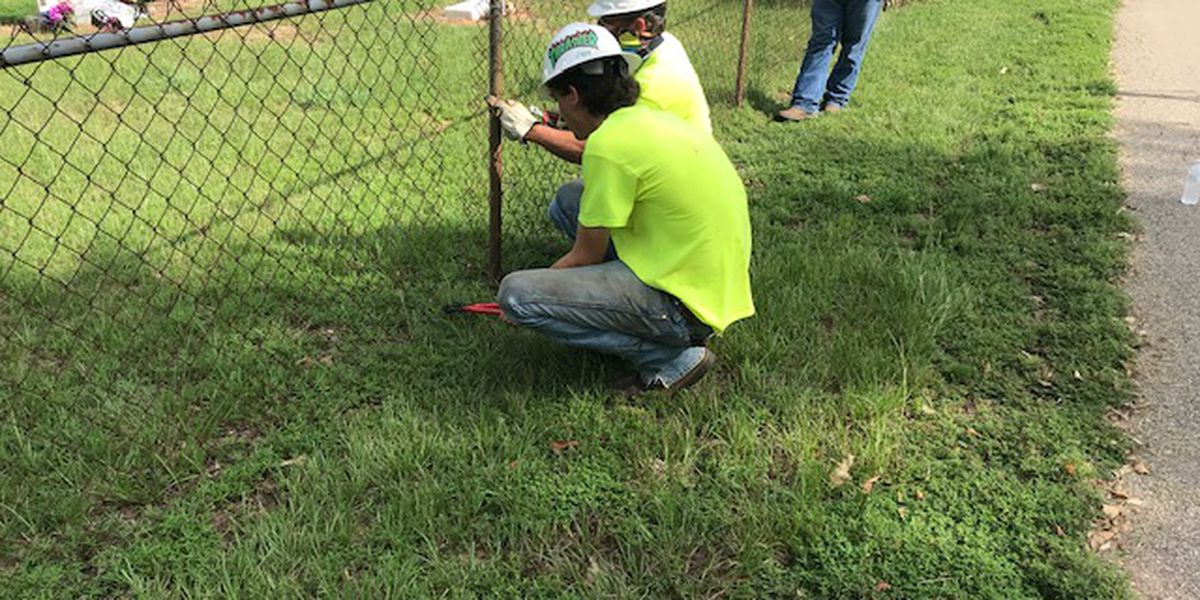 Work begins to remove fence that once divided segregated Mineola cemetery