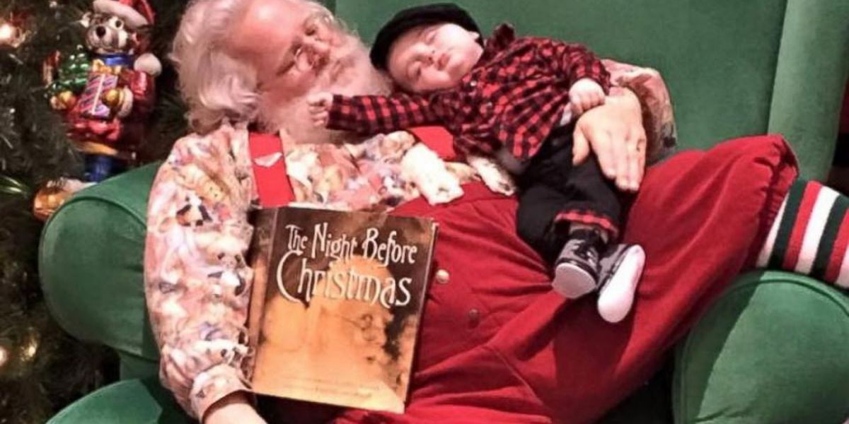 Santa Claus snoozes with baby in adorable photo session